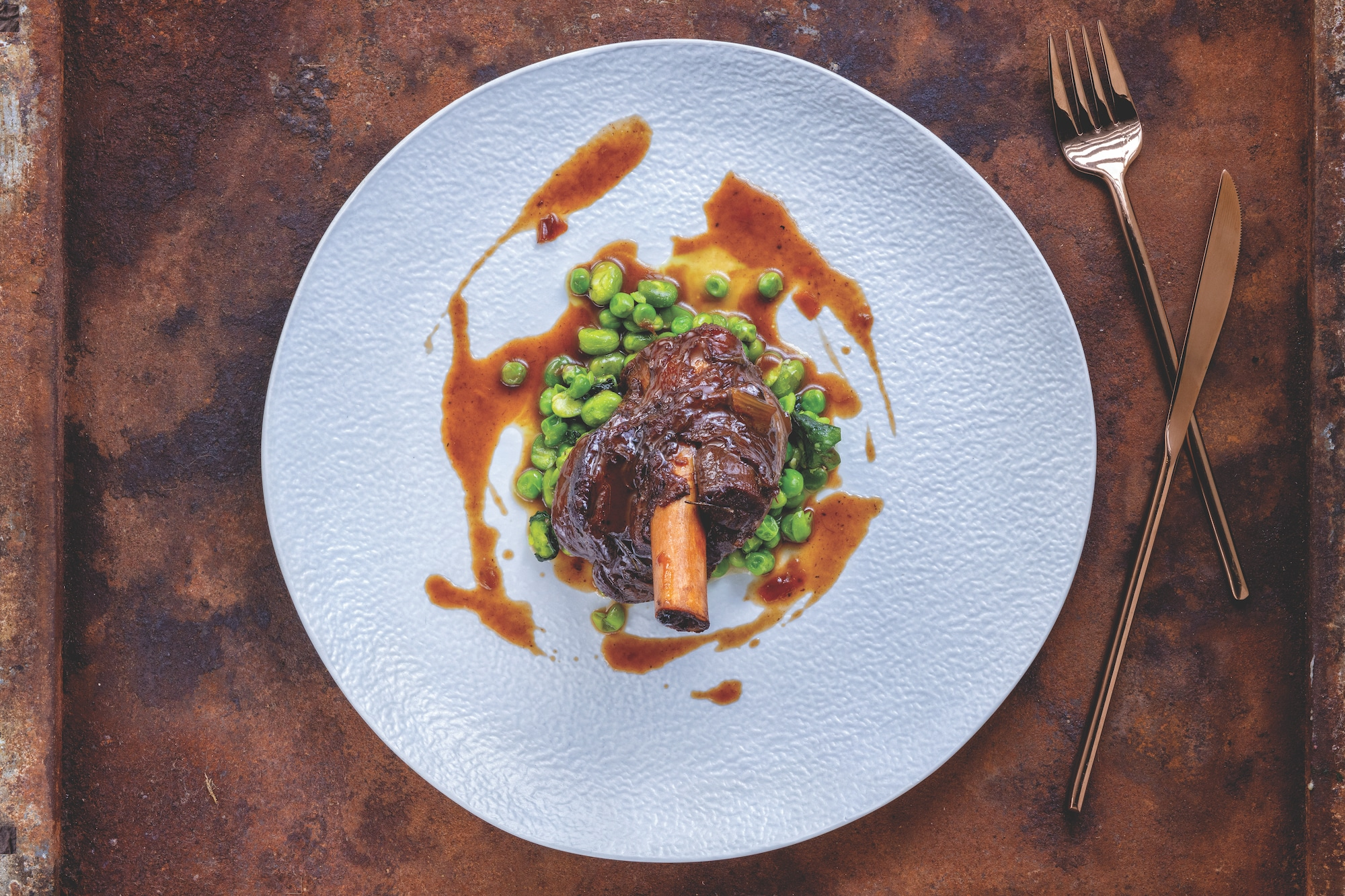 Braised lamb shank with broad beans, peas and mint